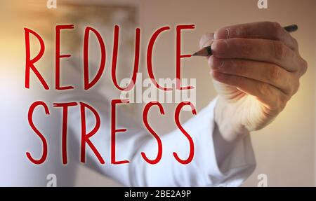 Doctor's hand writing words text Reduce Stress,,medical concept - Stock Photo