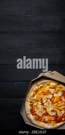 Pizza margherita in an open delivery box, dark backdrop with text space. Delivery foods, takeaway food concept: pile of pizza boxes on black wood back - Stock Photo