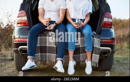 Close-up shot of feet of a woman and a man sitting in the car trunk on a check blanket, holding glasses of white wine, wearing similar clothes - Stock Photo
