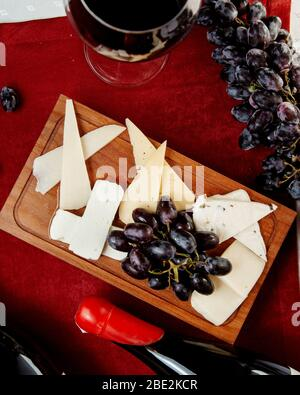 different types of cheeses and grapes and a glass of red wine - Stock Photo