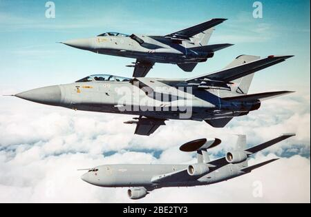 An air to air photograph showing two British Royal Air Force Panavia Tornado fighters, together with a Royal Air Force Boeing E-3D Sentry AWACS. - Stock Photo