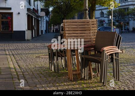 Stack of outdoor chairs of pub, cafe and restaurant shutdown during quarantine from contagion of COVID-19 on walking street in old town. - Stock Photo