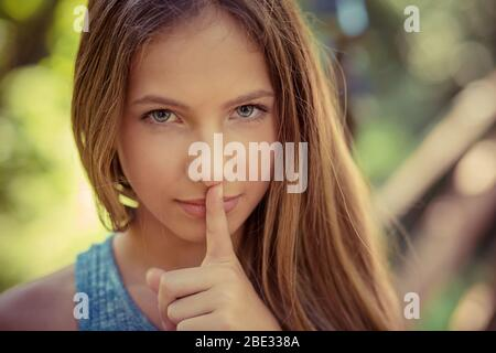Shh. Woman wide eyed asking for silence secrecy with finger on lips hush hand gesture green park outdoor background Pretty girl placing fingers on lip
