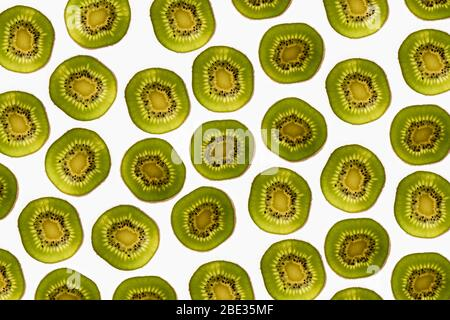 a beautiful image of an interesting pattern of kiwi fruit slices against a bright white background, flatlay