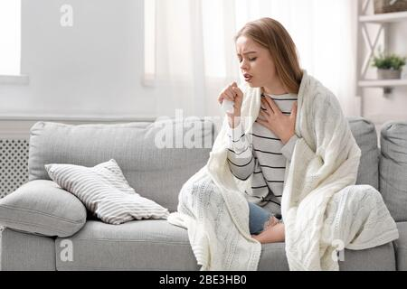 Young woman coughing hardly at home, free space - Stock Photo