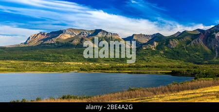 Panorama of mountain range along a lakeshore with blue sky and clouds, Waterton Lakes National Park; Waterton, Alberta, Canada