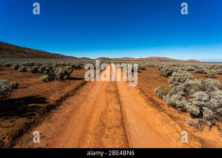 A long straight dirt track leading to the horizon through the desert in the Australian Outback - Stock Photo
