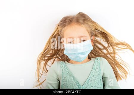 Coronavirus and Air pollution pm2.5 concept. Little russian girl with closed eyes wearing mask for protect during covid-19 quarantine. Prevention - Stock Photo