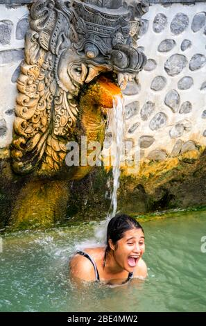 Vertical portrait of a woman underneath the hot springs at Banjar hot Springs in Bali, Indonesia.