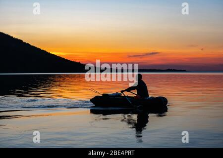Fisherman in an inflatable boat floats on the lake. Silhouette on a sunset background. Imantau lake. Kazakhstan - Stock Photo