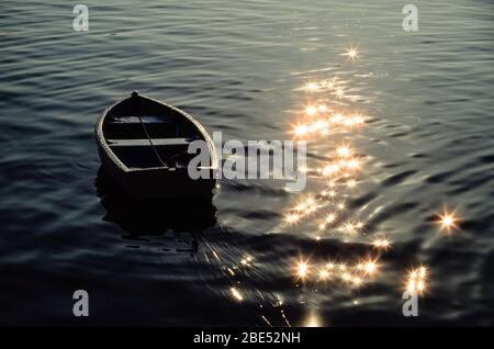 Small moored rowing boat with sparkling starburst water reflections in St Ives Harbour, Cornwall, England, UK.