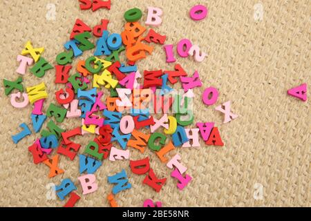 Multi coloured wooden letters in red, green, blue, pink & yellow. The letters are a childrens toy & are scattered on the floor. They are a fun way to - Stock Photo