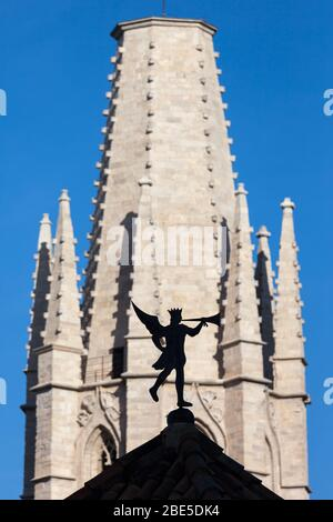 Weather vane trumpeting angel silhouette on roof top with Church of Sant Feliu (Saint Felix) tower in the background in Girona, Catalonia, Spain - Stock Photo