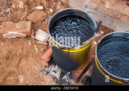 Bitumaning the mastics in yellow jars. Material for waterproofing the foundation. The mastika in the jars is heated on fire.
