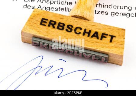 Ein Stempel aus Holz liegt auf einem Dokument. Deutsche Aufschrift: Erbschaft