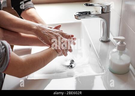 Mother teaching her daughter how to properly wash their hands with soap to prevent coronavirus infection