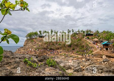 Horizontal view of tourists walking around Angel's Billabong on Nusa Penida, Indonesia. - Stock Photo