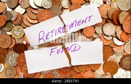 The words retirement fund written in purple pen on white paper, the paper is ripped across the words retirement fund the paper is on top of hundreds o - Stock Photo