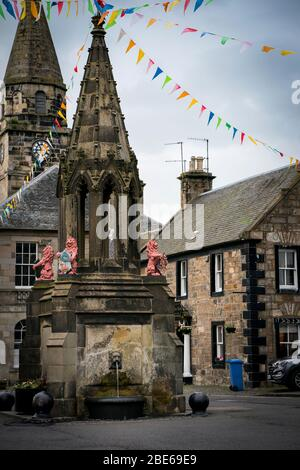 Bruce Fountain with festive colored flags above it, site of famous Outlander tv series scene when Jaime's ghost watches Claire in the adjacent inn win - Stock Photo