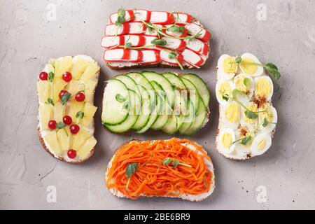 Five sandwiches on toast with fresh carrots, cucumbers, pineapple, red currant, crab sticks and quail eggs with peas microgreens on gray background - Stock Photo