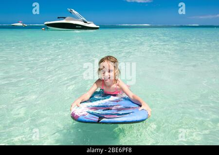 Little baby girl - young surfer with bodyboard has a fun on small ocean waves. Active family lifestyle
