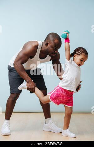 Father holding daughter by the leg while she tries to maintain balance