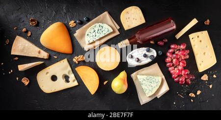 Cheese flat lay panorama. Many different cheeses, shot from the top on a black background - Stock Photo