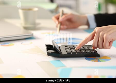 Close up of executive woman hand calculating with calculator comparing graphs sitting on a desk in the office - Stock Photo