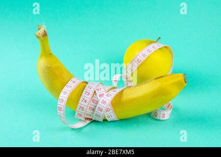 Different types of fruit, such as apples and bananas lie on a single-footed base and are wrapped in a measuring tape - concept for healthy weight loss - Stock Photo