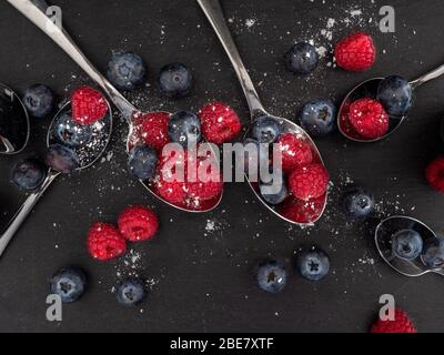 Looking down on a flat lat of raspberries and blueberries on a slate background