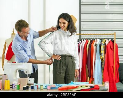 Fashion designer room, man and woman working in home base cloth design business. Men's tailors are measuring the length from the shoulders, elbows to - Stock Photo