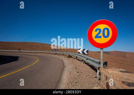 A speed limit sign reading '20' on high contrast yellow and red against clear blue sky on the National Road 9 across the Tizi'n-Tinififft pass. - Stock Photo