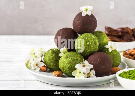 Green matcha energy balls or energy bites with energy balls in chocolate glaze with spring flowers. Healthy vegan diet snacks. Food styling. close up