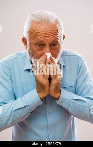 Portrait of senior man who is having allergy and blowing nose. - Stock Photo