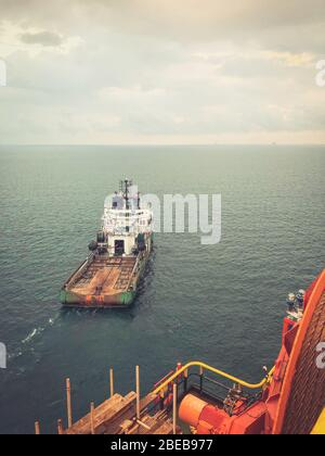 Balikpapan, Indonesia - October 2019: Singaporean offshore supply and anchor handling vessel from POSH, working on dynamic positioning close to a rig
