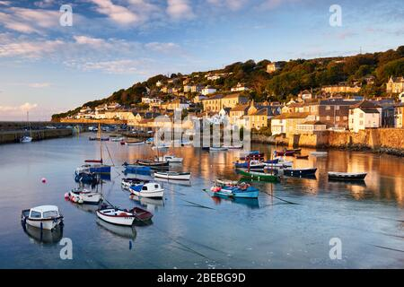 Morning sun lighting up the cottages along the waterfront of Mousehole harbour, the picturesque cornish village situated in West Cornwall - Stock Photo