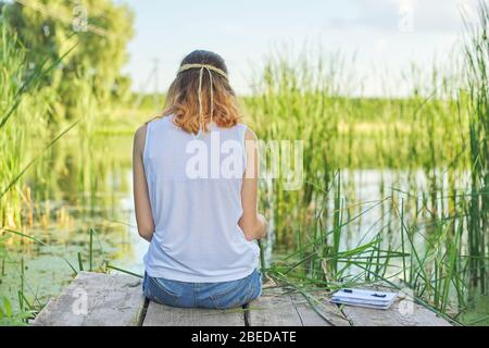 Young woman sitting with her back on wooden pier, enjoying picturesque view of lake water, relaxing in nature on sunny summer day, copy space