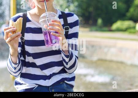 Street food, teenager girl eating sandwich and drinking drink from glass with straw.