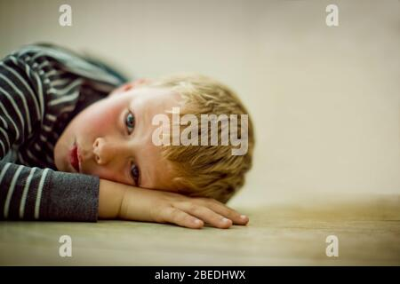 Portrait of a young boy lying on the floor. - Stock Photo