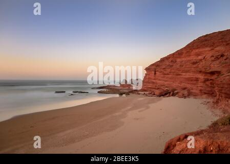 Landscape of Legzira Beach with its natural arches at the coast of Atlantic ocean. Legzira Beach is located on the ocean coast of Morocco, in Sidi Ifn - Stock Photo