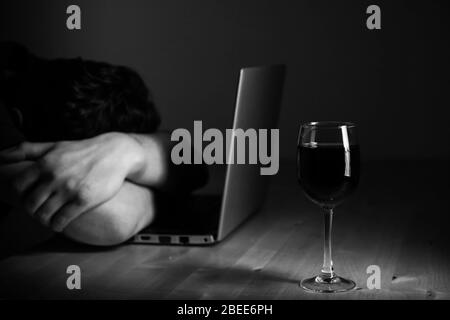 Home office and alcoholism problem - depressed man sitting in front of computer, he hide his face. Wine glass on the table