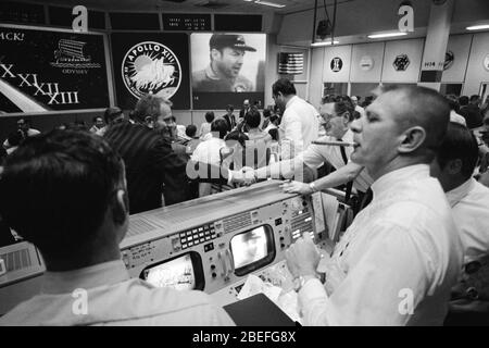 Deke Slayton (in the black shirt, left of center) director of flight crew operations and Chester M. Lee shake hands in Mission Control, while Rocco Petrone watches Apollo 13 commander Jim Lovell on the screen. Apollo 13, launched on April 11, 1970, was NASA's third crewed mission to the moon. Two days later, on April 13, while en route to the lunar surface, a fault in the electrical system of one of the Service Module's oxygen tanks produced an explosion that caused both oxygen tanks to fail and also led to a loss of electrical power. With the mission aborted, a dedicated team in the Apollo Mi - Stock Photo