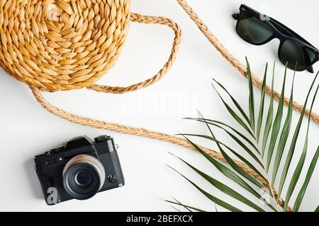 Summer fashion female outfit with rattan handbag, vintage camera, sunglasses, tropical palm leaf on white table. Travel, holiday, vacation concept. Fl