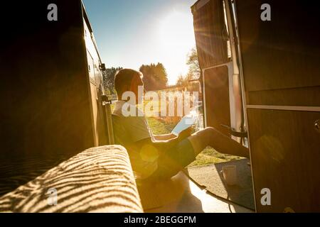 Portrait of careless man with tablet pc during holidays camping in his van