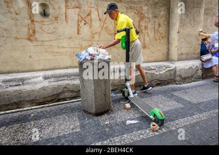 PRAGUE - JULY 20, 2019: A man putting litter into an over flowing bin next to an electric scooter for hire, on a street in Prague - Stock Photo