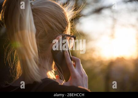 Backlit rear view of young woman talking on cell phone outdoors in park at sunset. Girl holding mobile phone, using digital device, looking at setting