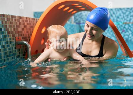 Very interesting active training in swimming pool. Little cute boy is learning how to float with his supportive mother. Concept of healthy family