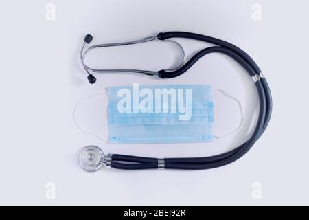 COVID-19, 2019-nCov novel coronavirus concept. Creative composition with stethoskope and disposable medical mask. Top view. - Stock Photo