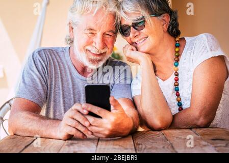 Happy beautiful senior old couple do a phone call with modern online technology device - retired cheeful people together forever with love and friends