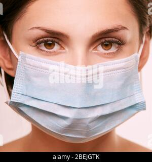 Beautiful young girl in medical breathing mask. Anti virus and dust protect. - Stock Photo